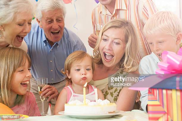 baby girl surrounded by family blowing out candle on birthday cake - surrounding stock pictures, royalty-free photos & images