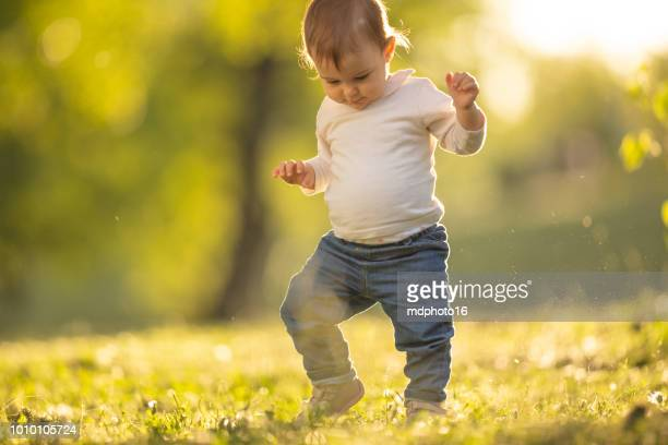 menina tomando seu primeiro passos em um parque - primeiros passos - fotografias e filmes do acervo
