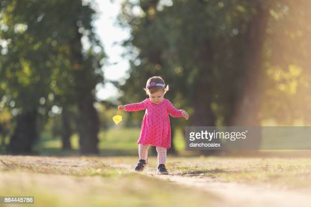 Baby girl taking her first steps outdoors