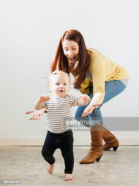 Baby girl (12-17 months) walking while mother assisting her