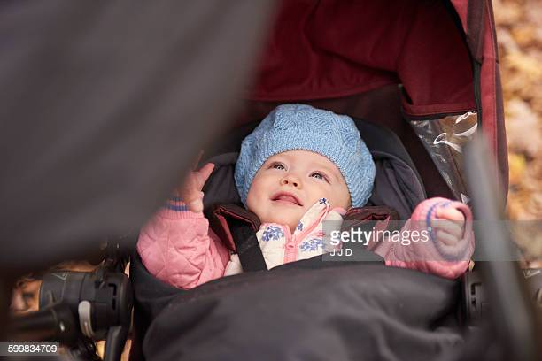 Baby girl wearing blue hat looking up from baby carriage