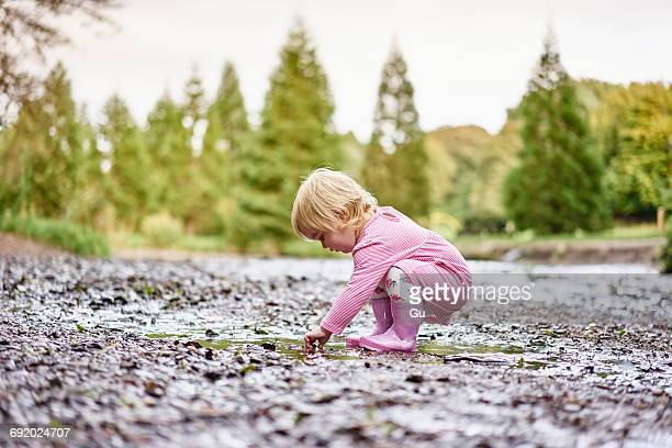 baby girl wearing rubber boots playing in muddy puddle - bent over babes stock pictures, royalty-free photos & images