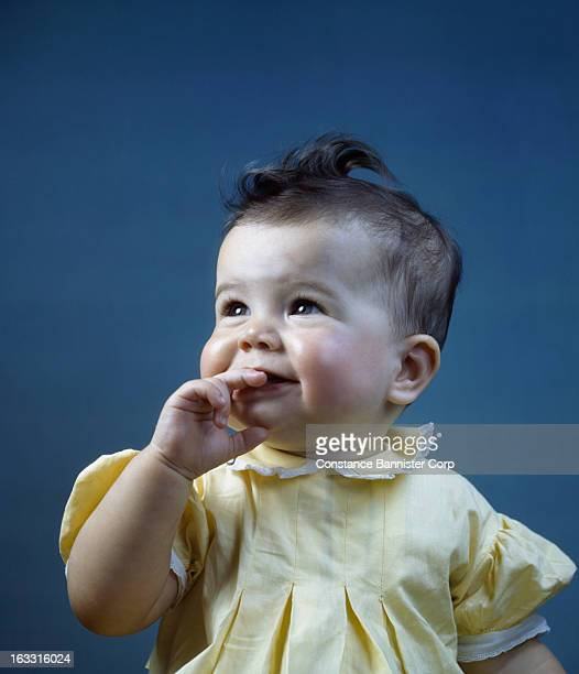 Baby girl wearing yellow dress with hand in mouth New York City USA