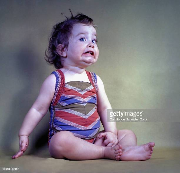 Baby girl with a scared face wearing a bathing suit New York City USA
