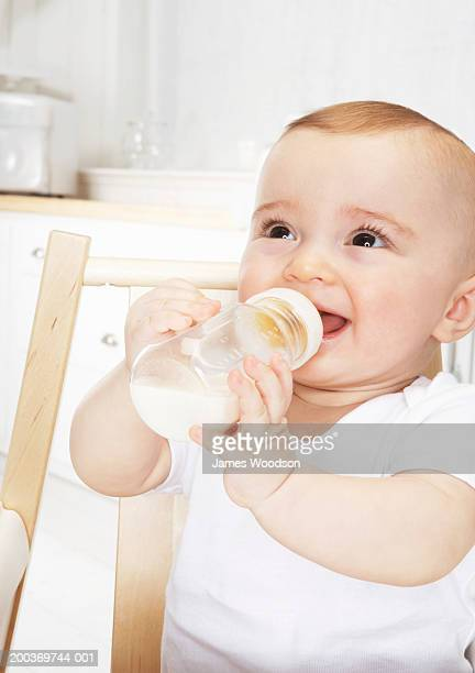 Baby girl (6-9 months) with bottle in high chair smiling, close-up