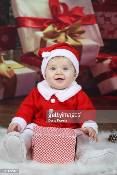 baby girl with christmas clothes enjoys a christmas present - taille naine photos et images de collection