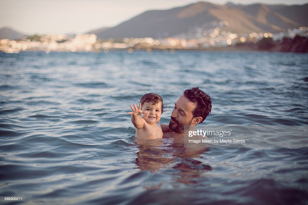 Baby girl with dad having a swim at the beach : Foto stock