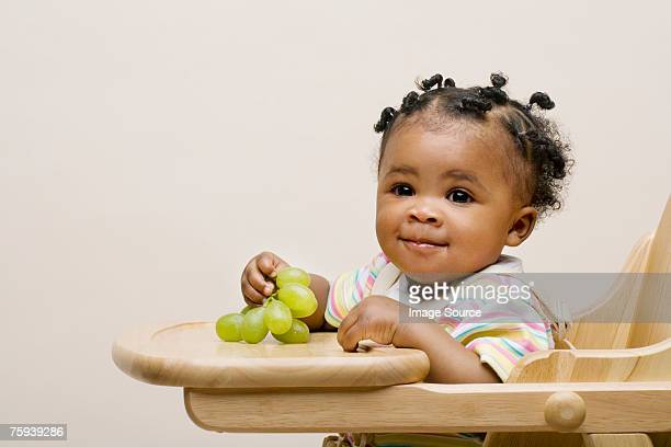 Baby girl with grapes