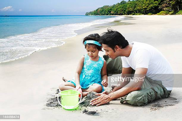 Baby girl with her father playing with sand at a beach