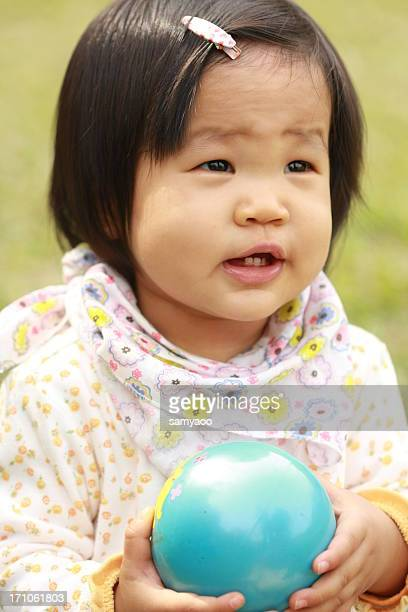 Baby girl with plastic ball in hands
