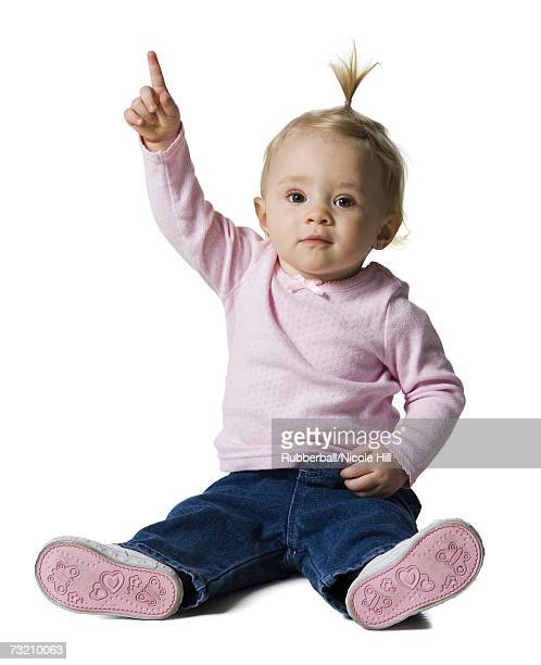 baby girl with ponytail pointing up - baby pointing stock photos and pictures