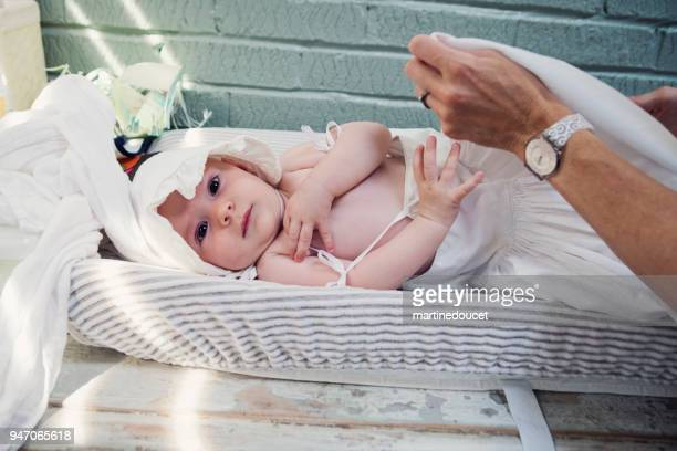 Baby girl with white lace bonnet on changing table.