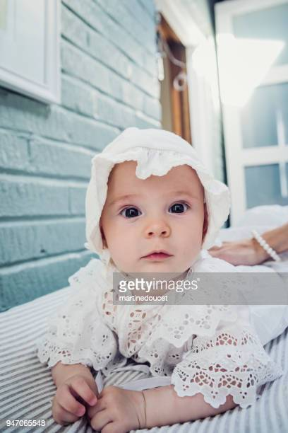 Baby girl with white lace dress lying on stomach.