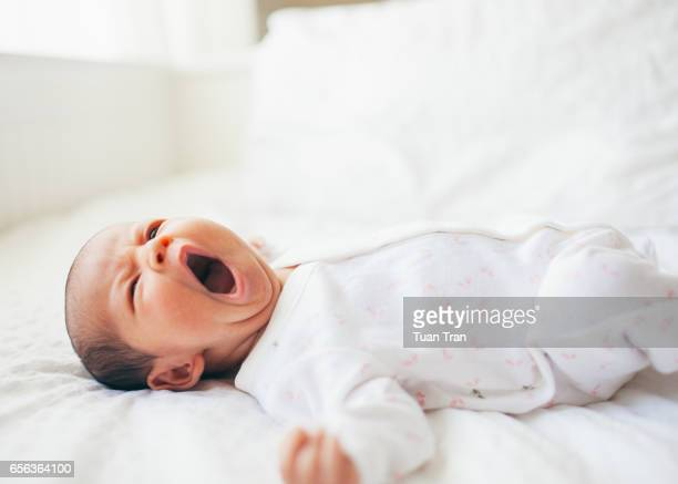 Baby girl yawning on bed