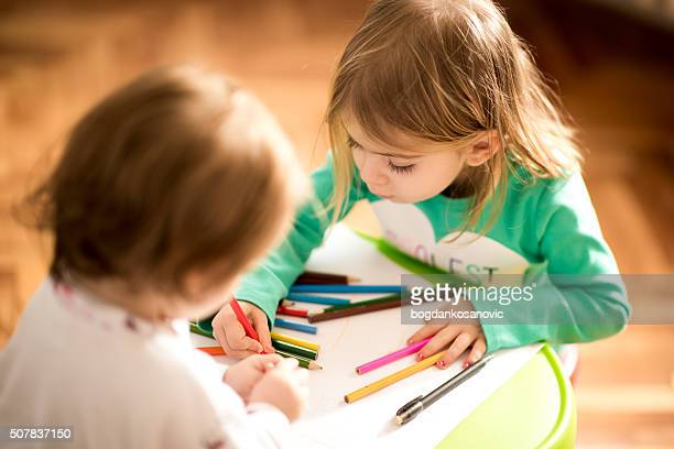 Baby girls at home learning to draw