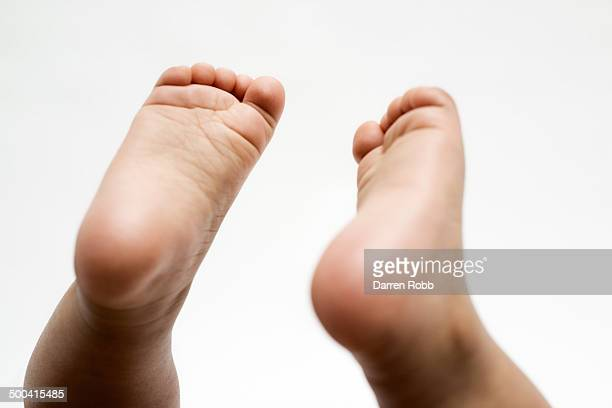 baby girl's feet raised in the air - human foot stock pictures, royalty-free photos & images