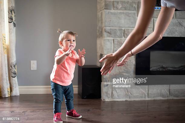 Baby girl's first step with her mother