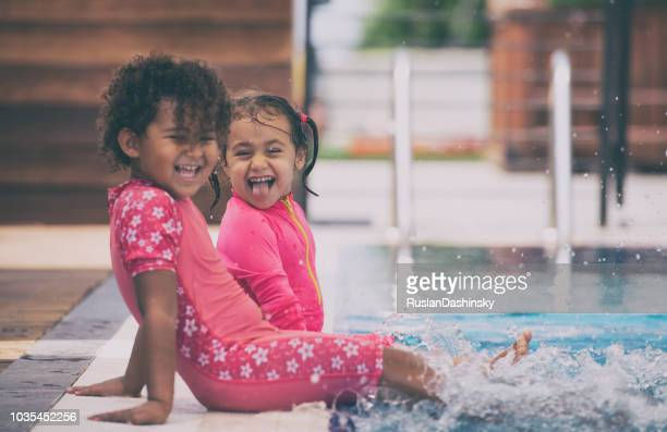baby girls having fun in the swimming pool. - kids pool games stock pictures, royalty-free photos & images