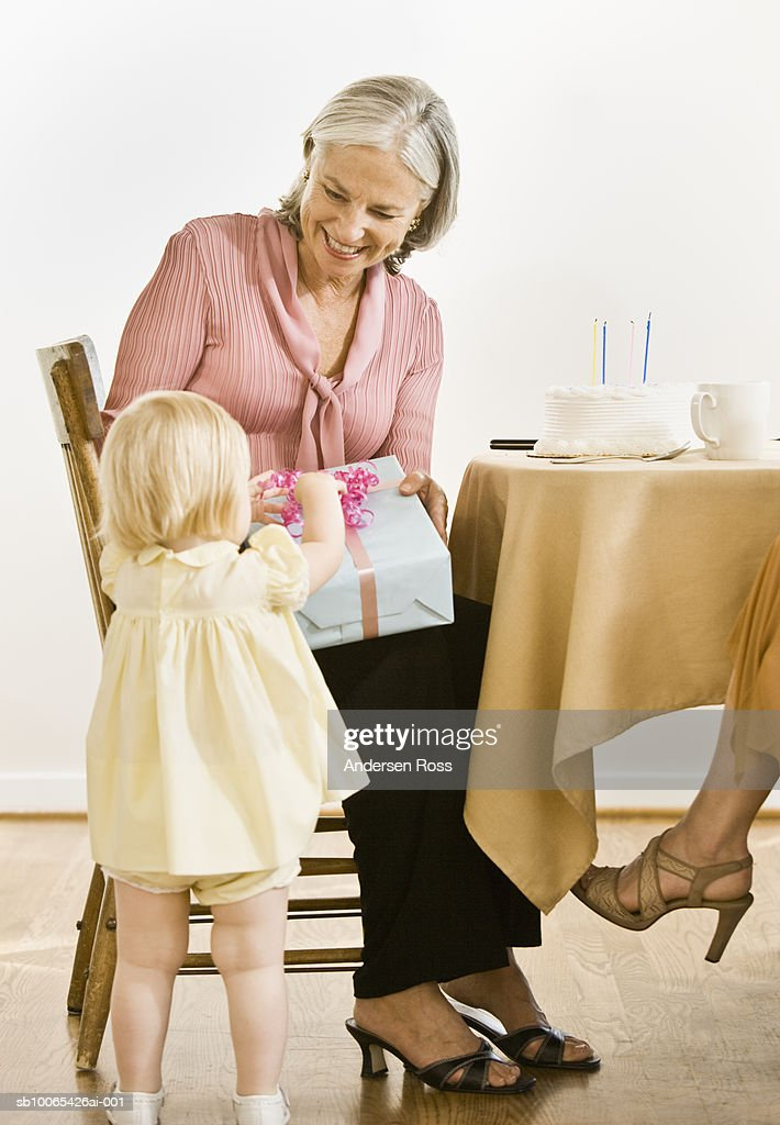 Baby granddaughter (9-12 months) giving gift to grandmother : Foto stock