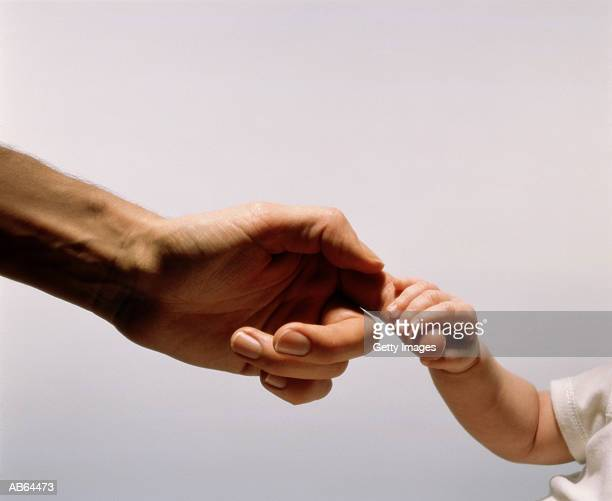 Baby hand holding fathers finger