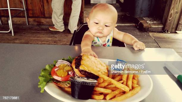 Baby Having Food On Table At Restaurant