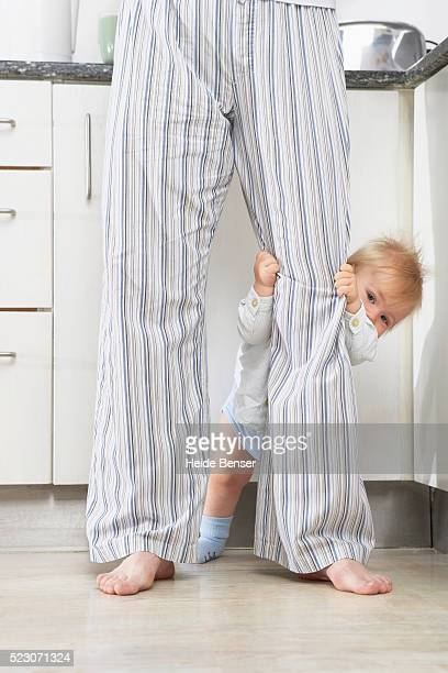 Baby hiding behind their father's leg