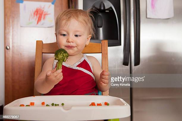 Baby holding a piece of broccoli