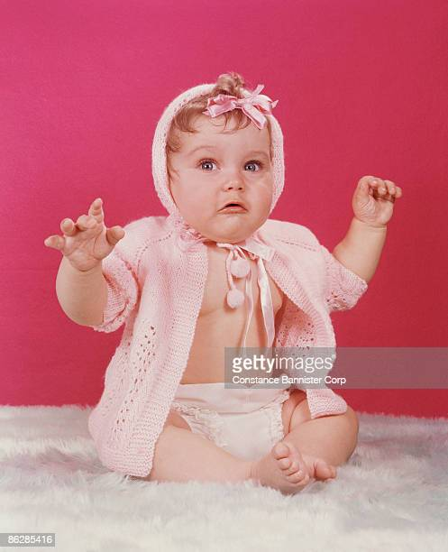 baby holding arms up with surprised expression - constance bannister stock photos and pictures