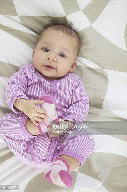 Baby holding foot.