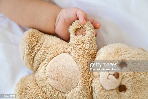 Baby holding hands with teddy bear, cropped