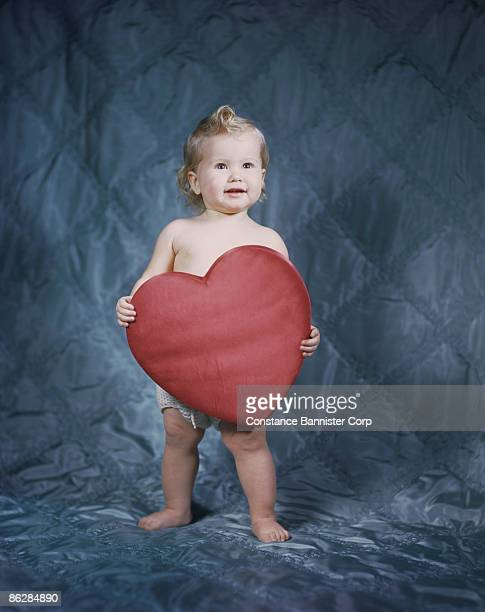 Baby holding heart shaped pillow