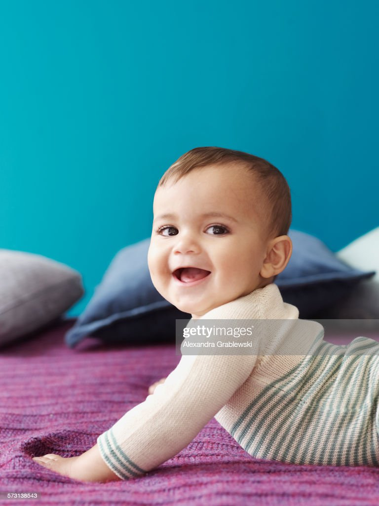 Baby Holding Himself Up and Smiling : Stock Photo