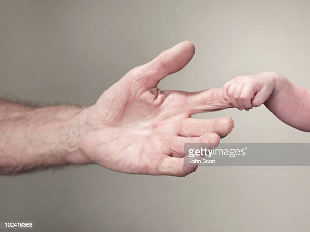 Baby holding man's finger, close-up of hands