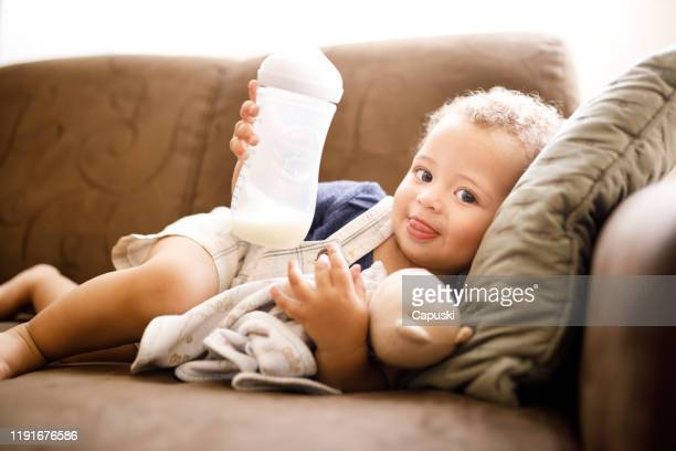 baby holding milk bottle - milk bottle stock pictures, royalty-free photos & images