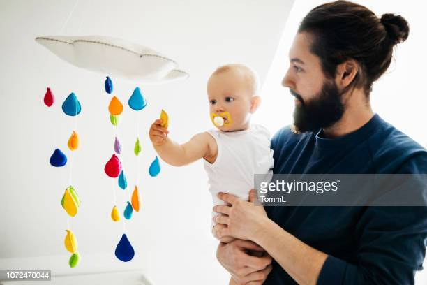 baby papa vasthouden tijdens het spelen van wth mobile - mobile stockfoto's en -beelden