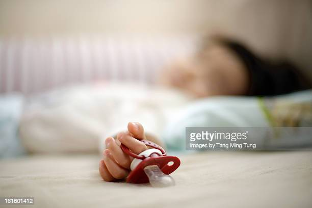 baby holding pacifier in her hand sleeping soundly