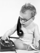 baby boy holding retro telephone trying