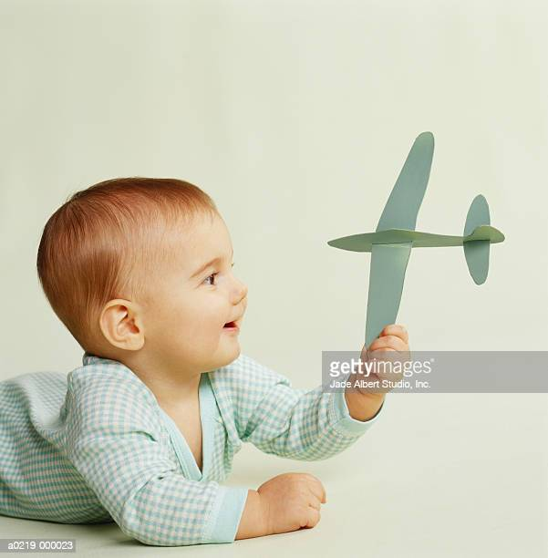 Baby Holding Toy Airplane