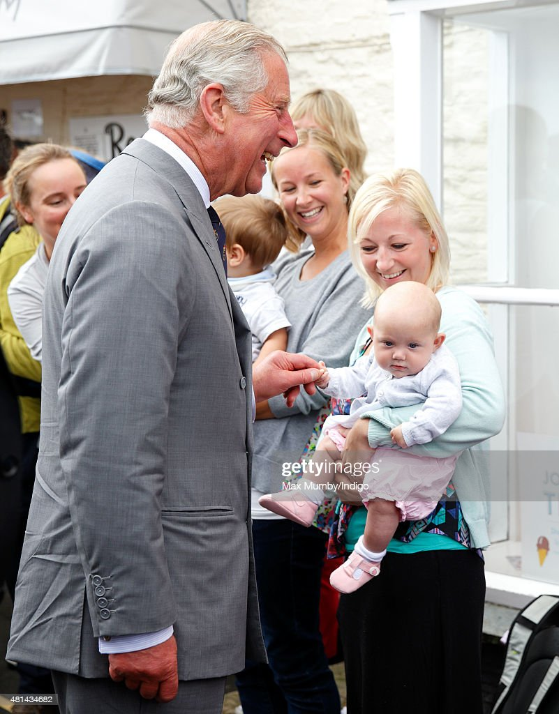 A baby holds onto Prince Charles, Prince of Wales' finger during a walkabout as he and Camilla, Duchess of Cornwall visit Padstow on day 1 of their annual summer tour of Cornwall on July 20, 2015 in Padstow, England.