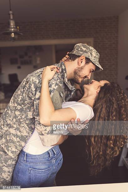 baby i'm home. soldier kissing his wife - military spouse stock pictures, royalty-free photos & images