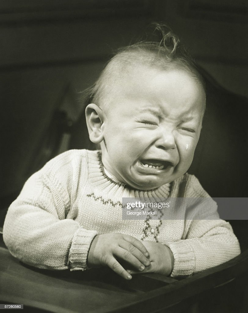Baby (9-12 months) in baby seat crying, (B&W), close-up : Stock Photo