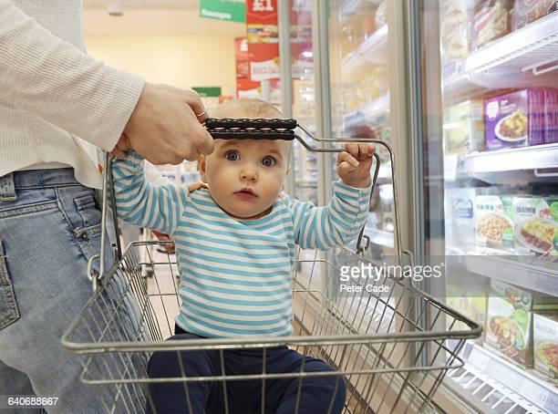 baby in basket in supermarket