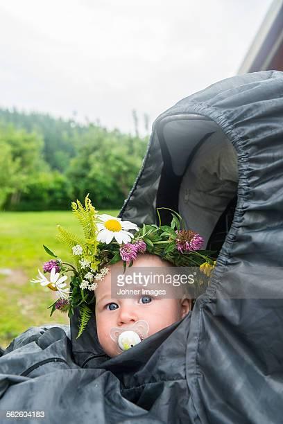 Baby in buggy wearing flower wreath
