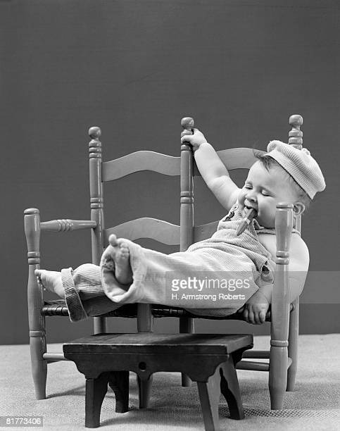 Baby In Corduroy Overalls And Cap, Smoking Cigar, And Lounging In 2-Seated Chair.