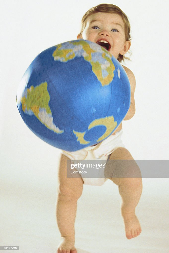 Baby in diapers holding inflatable globe : Stockfoto