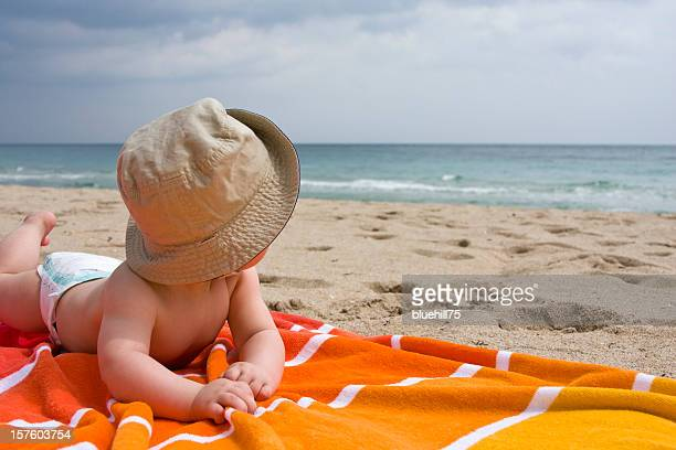 Baby in hat and diaper laying on orange towel at the beach