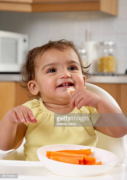 Baby in kitchen highchair eating carrot sticks