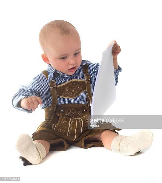 Baby in Lederhose-Trachtenmode beim Lesen
