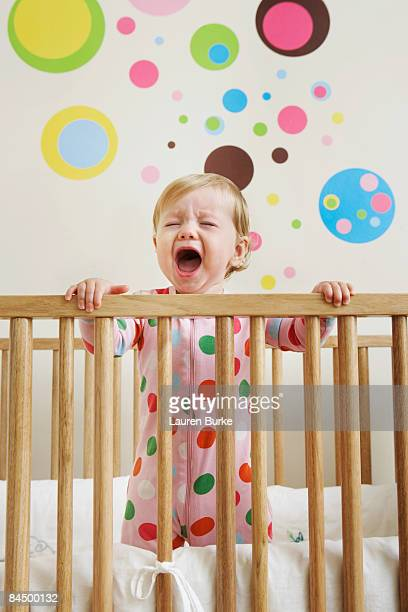 Baby in pajamas standing in crib crying