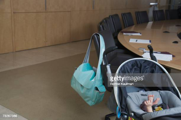 Baby in stroller and diaper bag over back of chair at conference table